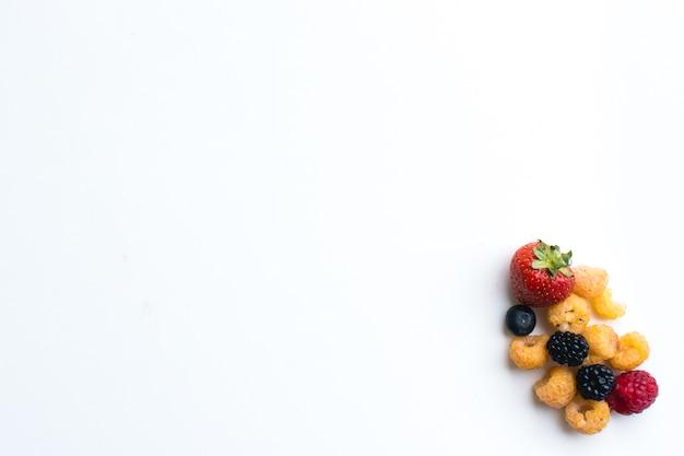 Tiro aéreo de bagas frescas saudáveis coloridas em um fundo branco
