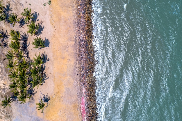 Tiro aéreo drone da bela praia de areia branca com coqueiros verdes e pedra