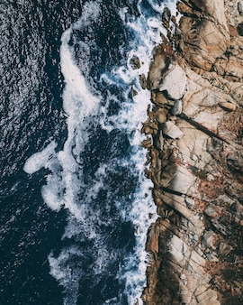 Tiro aéreo vertical da costa rochosa ao lado de um corpo de água com ondas espirrando as rochas