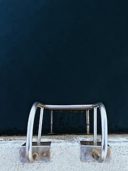 Tiro aéreo vertical de uma escada de prata em uma piscina