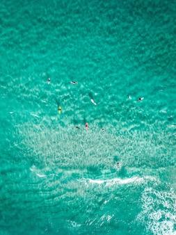 Tiro aéreo vertical surfistas com pranchas de surf em um mar azul claro