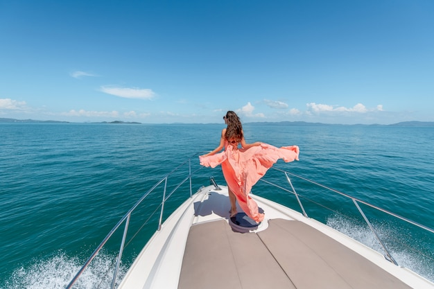 Tiro ao ar livre da adorável jovem mulher em um vestido rosa na borda do iate