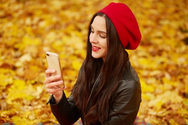 Tiro ao ar livre da menina adorável vestindo boina e jaqueta de couro no parque outono faz auto-retrato em seu celular