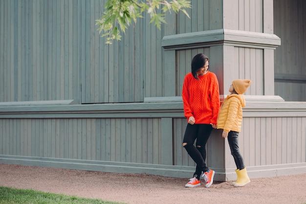 Tiro ao ar livre da mulher amigável segura a mão de filhas