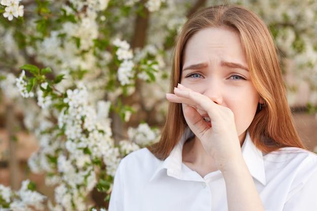 Tiro ao ar livre da triste estressada bela jovem fêmea esfrega o nariz como tem alergia a flor, veste camisa branca elegante, coloca contra árvore florescendo