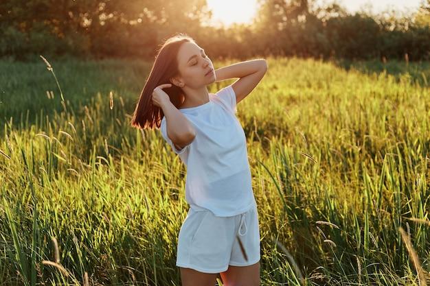 Tiro ao ar livre de atraente mulher de cabelos escuros, vestindo camiseta branca e curta olhando para longe, levantando os braços, posando em prado verde, apreciando o belo pôr do sol e a natureza.