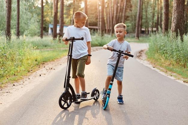 Tiro ao ar livre de dois irmãos vestindo roupas casuais, andando de scooters no parque de verão, passando o tempo feliz, se divertindo juntos de forma ativa, infância feliz.