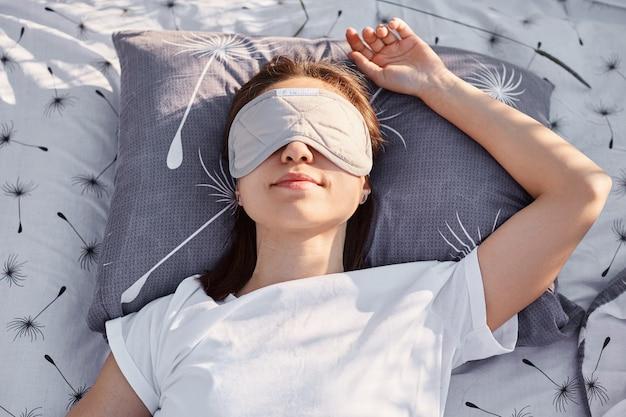 Tiro ao ar livre de jovem morena vestindo camiseta branca estilo casual e máscara de dormir deitada na cama e dormindo, aproveitando o ar fresco e o sol.