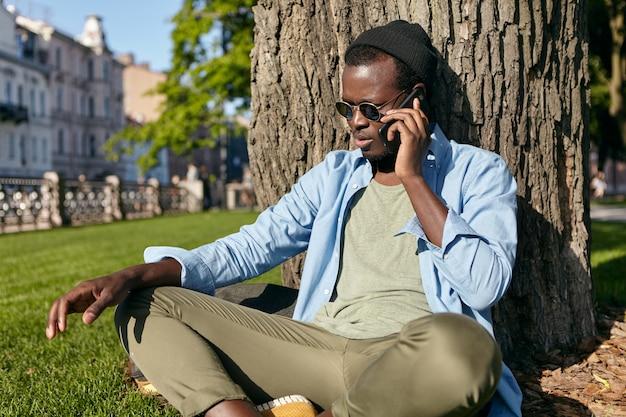 Tiro ao ar livre de macho de pele escura em óculos da moda, chapéu, camisa e calça, sentado de pernas cruzadas no gramado verde perto da árvore, passando seu tempo livre no parque, falando por telefone inteligente com o amigo