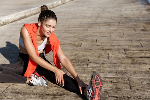 Tiro ao ar livre de mulher atraente fitness parecendo feliz esticando a perna antes de treino.