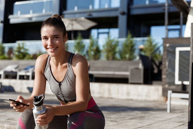 Tiro ao ar livre de mulher atraente fitness sentada com smartphone e água potável.