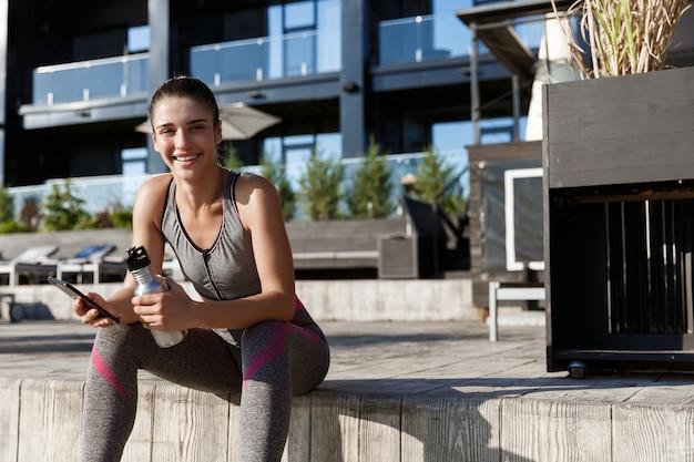 Tiro ao ar livre de mulher atraente fitness sentada com um telefone celular e água potável.