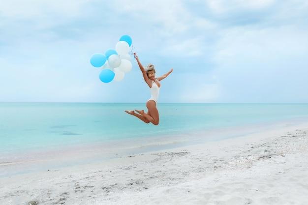 Tiro ao ar livre de satisfeito jovem fêmea com pele bronzeada, corpo esguio, usa biquíni vermelho e óculos de sol, coloca-se contra a maravilhosa vista para o mar, céu azul, goza de descanso no lugar do resort. pessoas e recreação