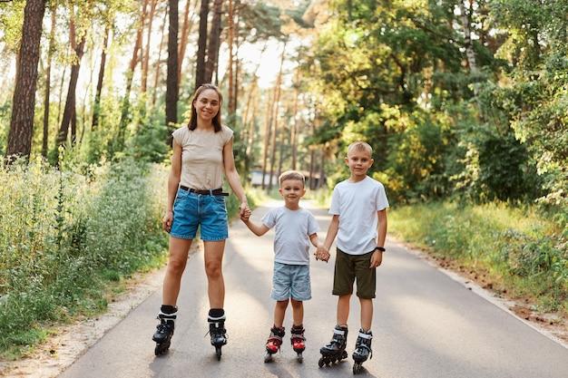 Tiro ao ar livre de sorrir mulher atraente com seus filhos pequenos em pé na estrada, no parque de verão e de mãos dadas, família andando de patins juntos, se divertindo, passatempo ativo.