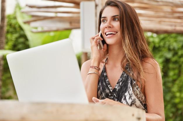 Tiro ao ar livre de um redator feminino bonito satisfeito resolve problemas via telefone celular, funciona no computador laptop, senta-se contra o interior do café com terraço aconchegante.
