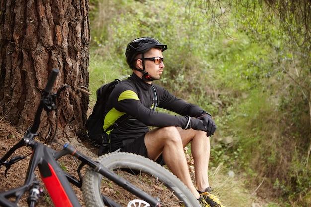 Tiro ao ar livre do triste e infeliz jovem ciclista vestindo roupas esportivas, capacete e óculos, sentado sob uma grande árvore com bicicleta elétrica quebrada, deitado no chão, esperando por amigos para ajudá-lo