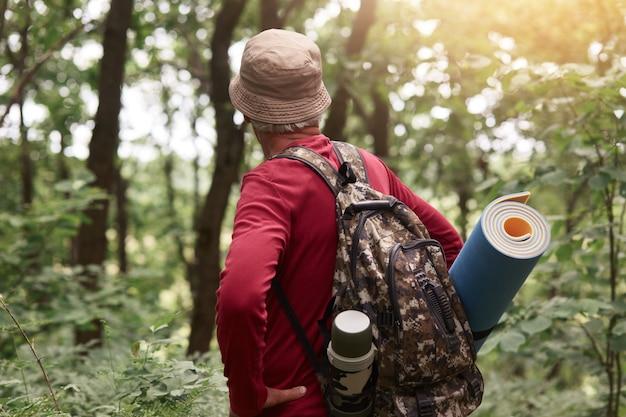 Tiro ao ar livre do velho homem tendo saco com garrafa térmica e almofada para dormir, usando chapéu bege e moletom vermelho, procurando aventuras na floresta sozinha, gosta de viajar e fazer caminhadas.