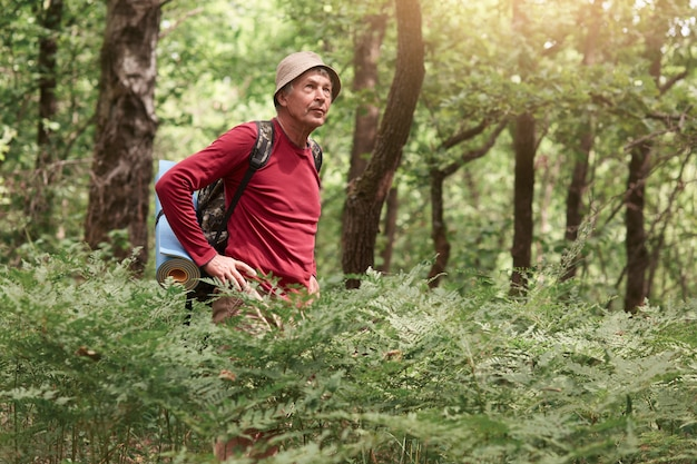 Tiro ao ar livre do viajante pensativo pensativo olhando de lado, sendo focado em sua viagem, procurando uma saída da floresta, usando chapéu bege