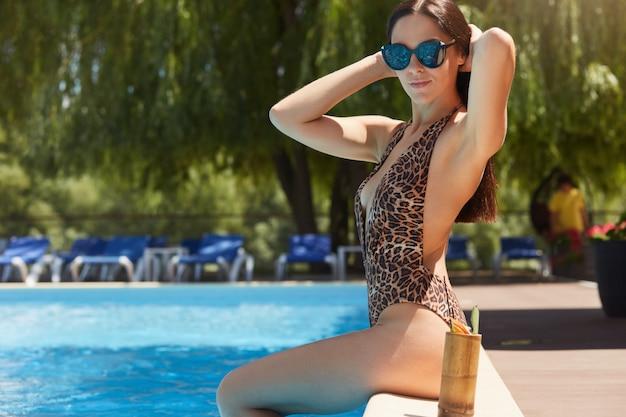 Tiro ao ar livre horizontal do terno e óculos de sol vestindo fêmeas atrativos relaxados de natação do leopardo, tocando em seu cabelo, sentando-se perto da piscina, passando o tempo fora. conceito de verão e férias.