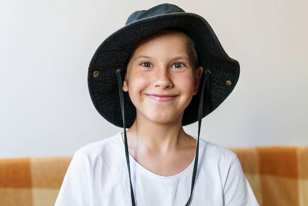 Tiro cândido de criança feliz com rosto sorridente, sentado no sofá, vestindo camiseta branca e panamá preto ...