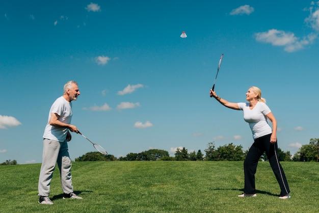 Tiro cheio, par, jogando tênis, ao ar livre