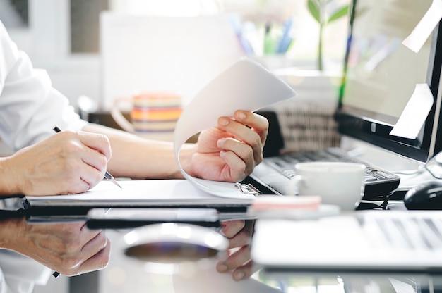 Tiro colhido da mão do homem usando lápis escrevendo na área de transferência enquanto está sentado na mesa do escritório e trabalhando com o computador.