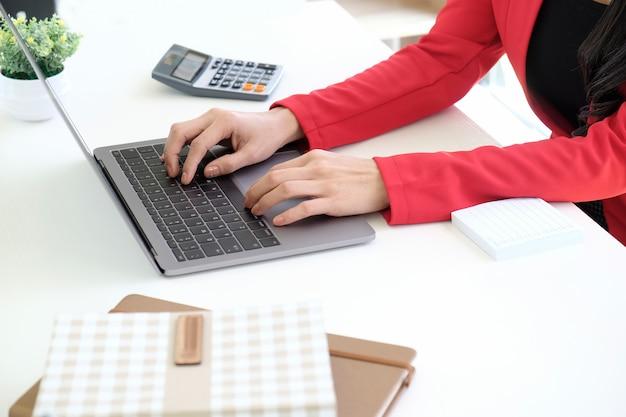 Tiro colhido da mulher de negócios que usa o portátil em sua mesa no escritório do estúdio.