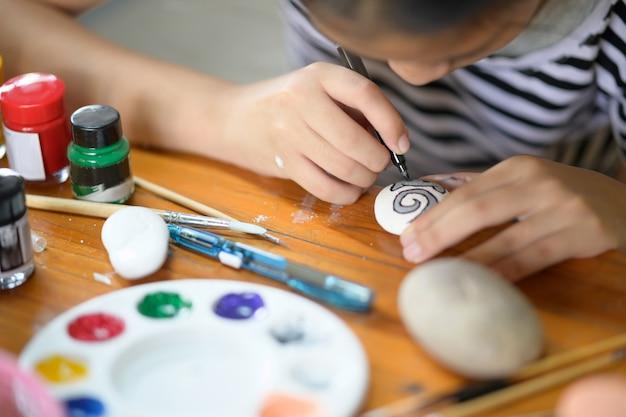Tiro colhido da pintura do artista da moça com cor de água na rocha.