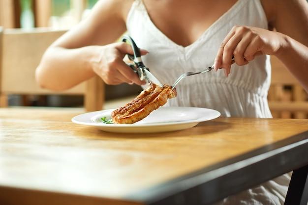 Tiro colhido de uma mulher que grelha o bife no restaurante que corta-o com tesouras que come o conceito com fome do jantar do café da fome do almoço do alimento.
