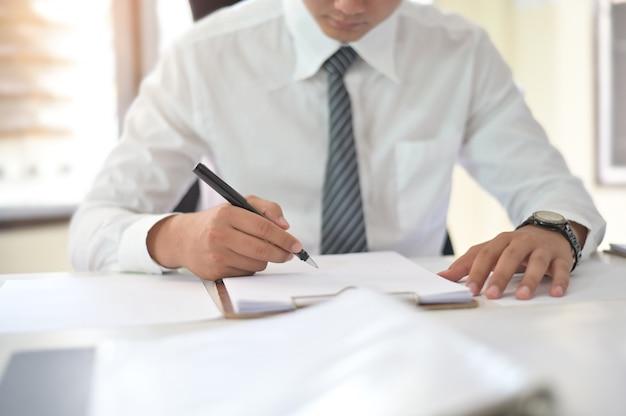 Tiro colhido do contrato de assinatura do homem de negócios que faz um acordo no local de trabalho do escritório.