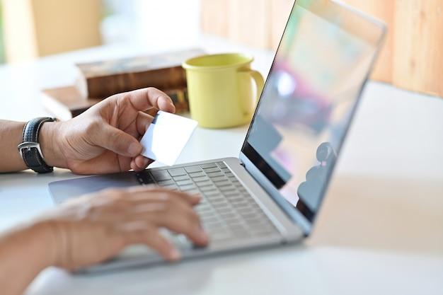 Tiro colhido do homem que usa o portátil e o cartão de crédito para o pagamento em linha.
