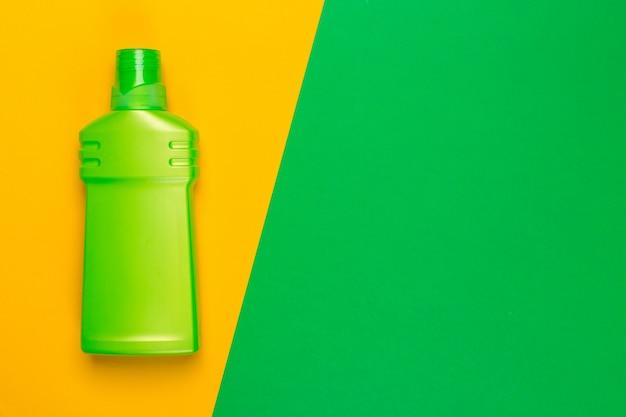 Tiro colorido brilhante de um recipiente plástico de produtos químicos domésticos. vista superior fundo verde e amarelo