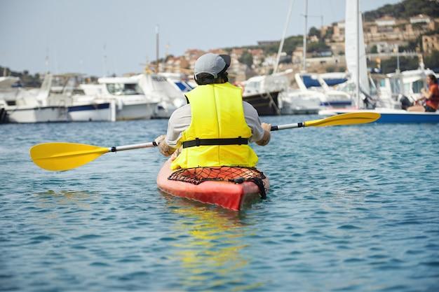 Tiro colorido de canoagem jovem em um colete de natação amarelo com remo parado no ar. bela paisagem de adorável porto com iates brancos e casas próximas na montanha.