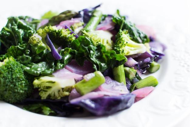 Tiro colorido vibrante de legumes sazonais primavera cozidos em um fundo branco