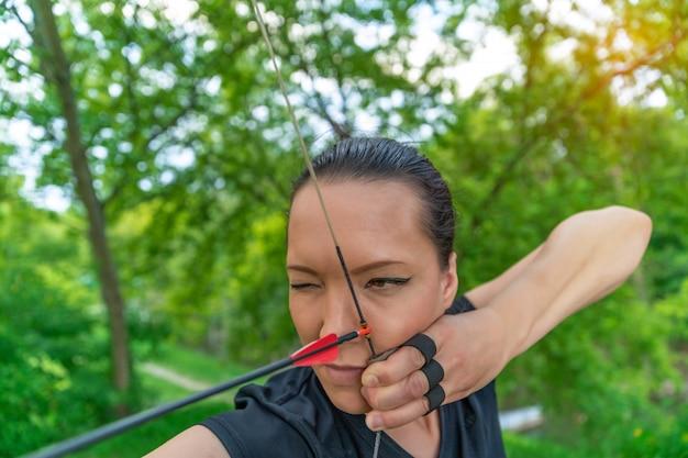 Tiro com arco, jovem mulher com uma flecha em um arco focado em atingir um alvo