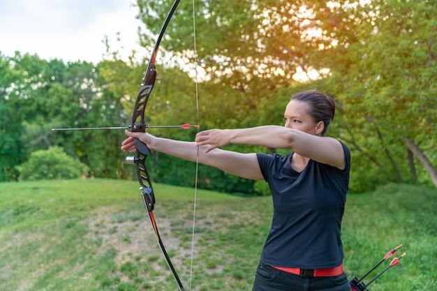 Tiro com arco na natureza, jovem mulher apontando uma flecha para um alvo