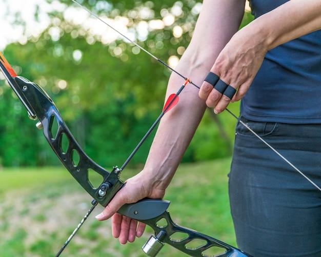 Tiro com arco, preparando-se para atirar uma flecha de um arco