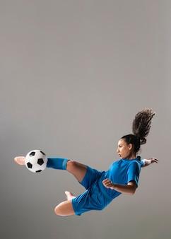 Tiro completo, atlético, mulher, chutando bola