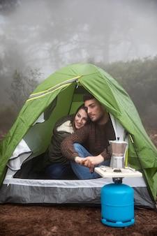 Tiro completo casal feliz sentado na tenda