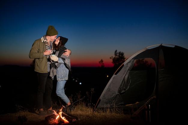 Tiro completo casal fofo beijando na natureza