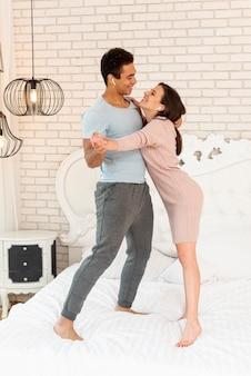 Tiro completo casal sorridente ouvindo música na cama