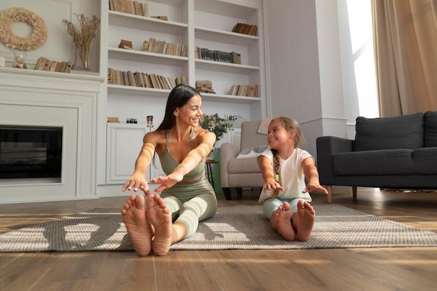 Tiro completo, criança e mulher fazendo ioga