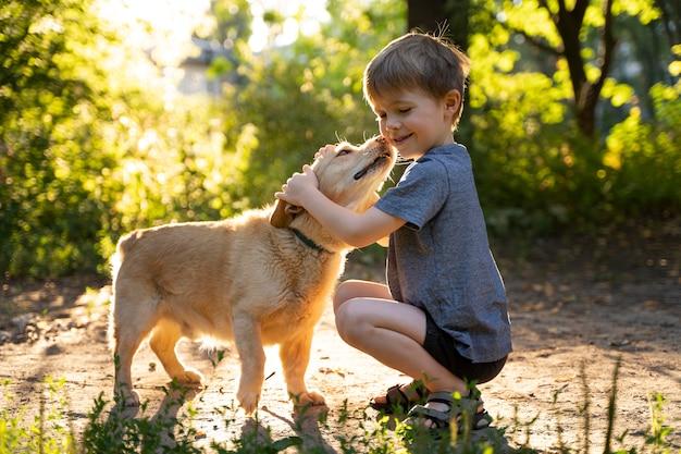 Tiro completo de criança abraçando um cachorro