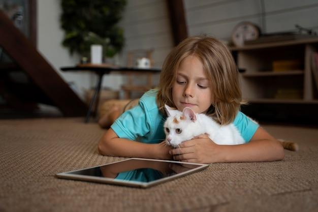 Tiro completo de criança e gato com tablet