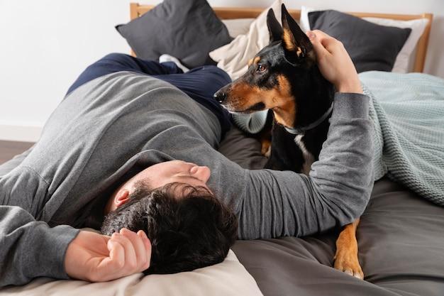 Tiro completo de homem e cachorro na cama
