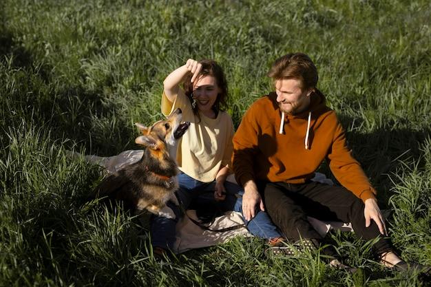 Tiro completo de homem e mulher com cachorro fofo