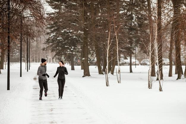 Tiro completo de homem e mulher correndo na floresta