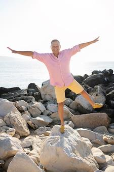 Tiro completo de homem posando sobre pedras