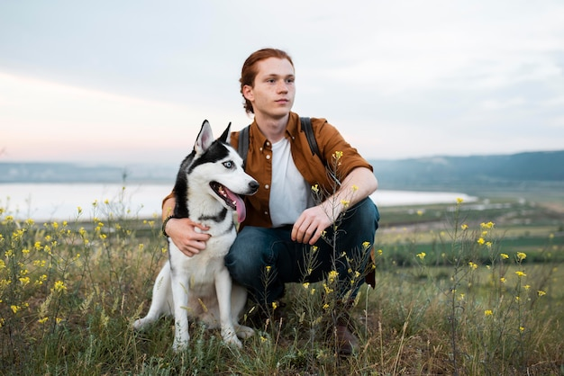 Tiro completo de homem viajando com cachorro na natureza