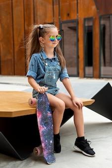 Tiro completo de menina com macacão azul